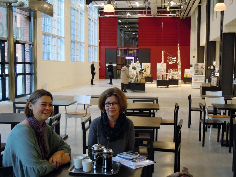 Jenny Findahl till vänster och Lena Engström till höger vid fikabordet på museitorget. I fonden ses entrén till länsmuseet och där står museichefen Carl-Magnus Gagge, i svart mot den vita väggen i svart med en besökare. Musieshopen har rea, vi handlar lite. Foto ChL.