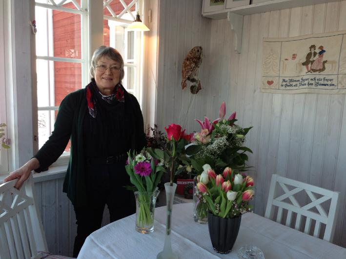 Karin Johansson på sin veranda bland blomstren.