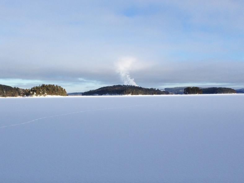 Revsundssjön, som på ngåot vis är lite lik Väsman i Ludvika. Stor sjö med blå höjder runtomkring. Det som ser ut som en rykande vulkan är bara rykande vattenånga från Gällösågens tork.